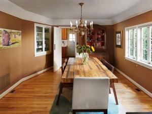Dining room wood floor chandelier window builtins