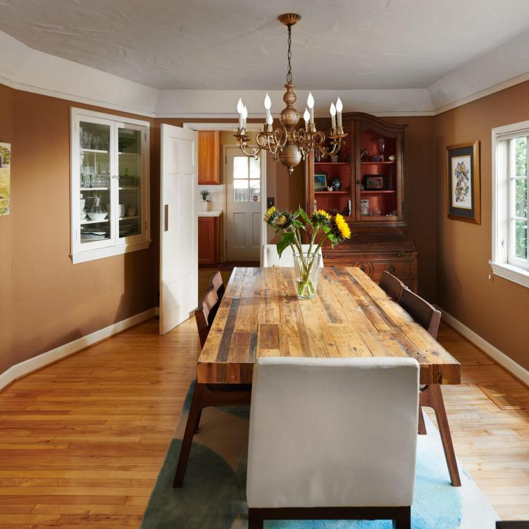 Dining room wood floor chandelier window builtins