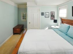bedroom with bed and windows and wood door coved ceilings