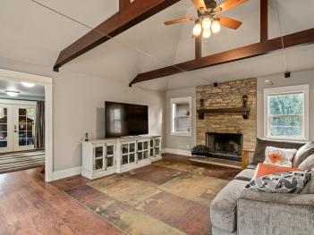 Living room with fireplace and exposed beam vaulted ceilings Tigard Oregon
