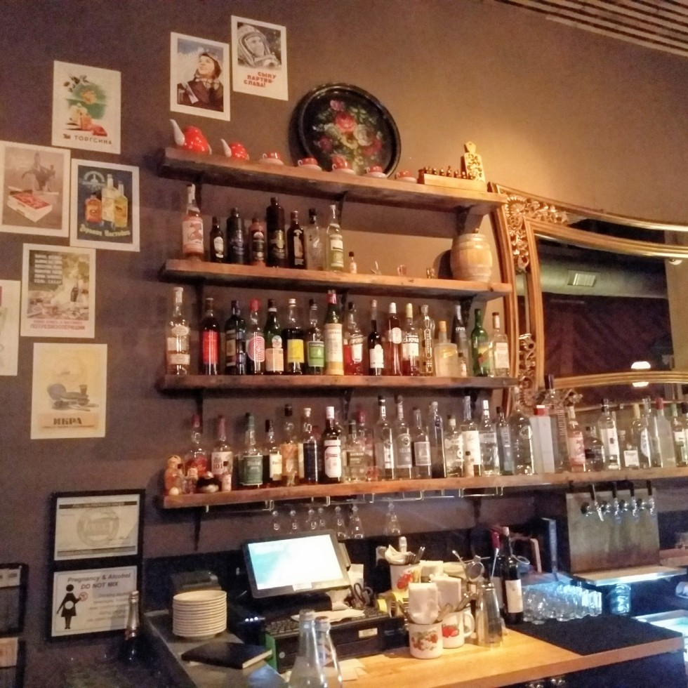 bar with bottles and a mirror at Kachinka