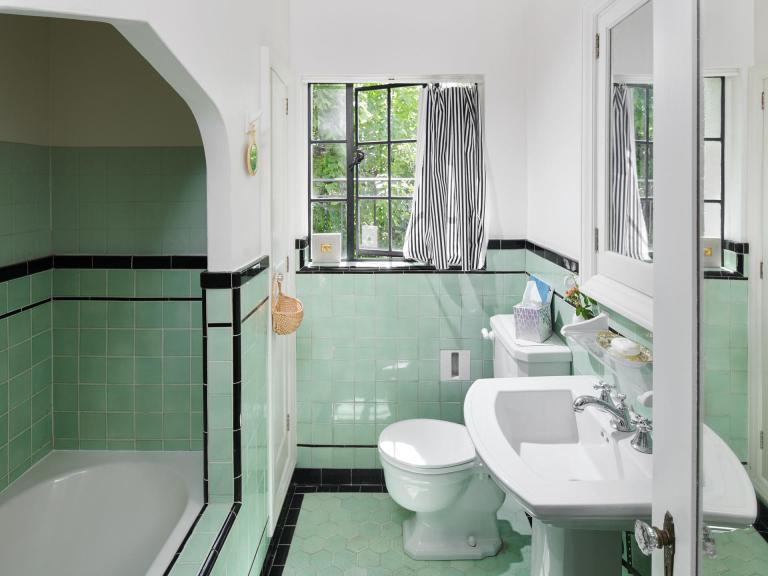 Vintage 1920s bathroom w/ pedestal sink, deco tiles and coved bath.