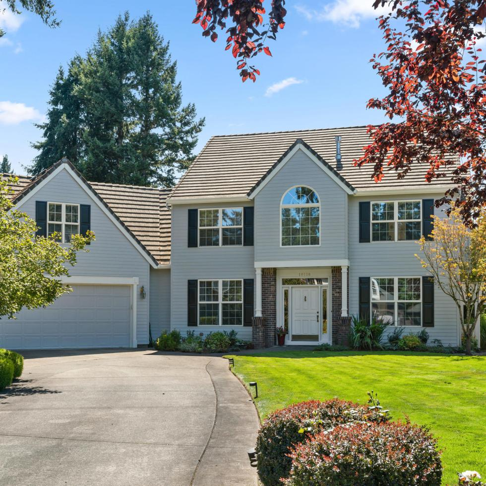 Exterior Traditional home in Tualatin with green grass and driveway up to garage