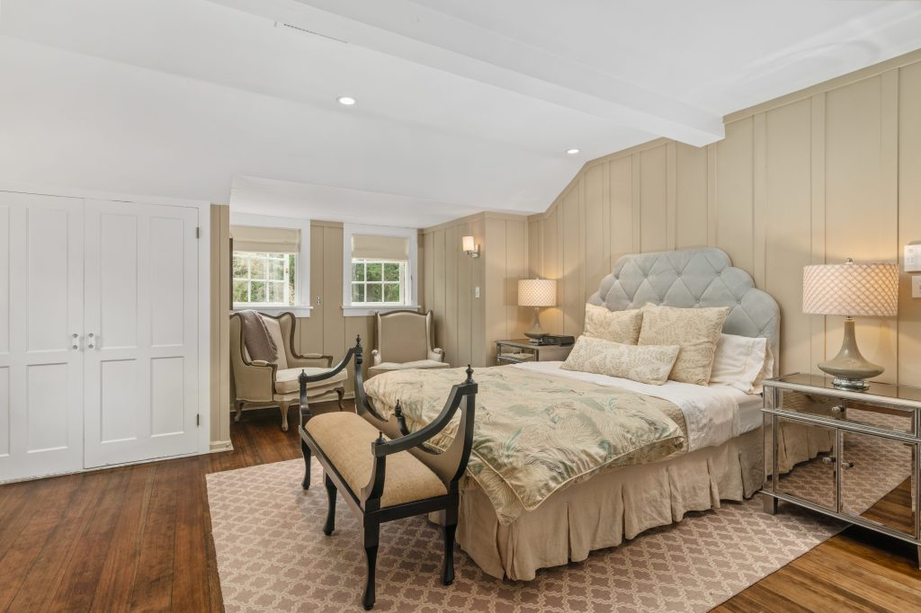 Master bedroom hardwood floors cozy bed beam ceilings