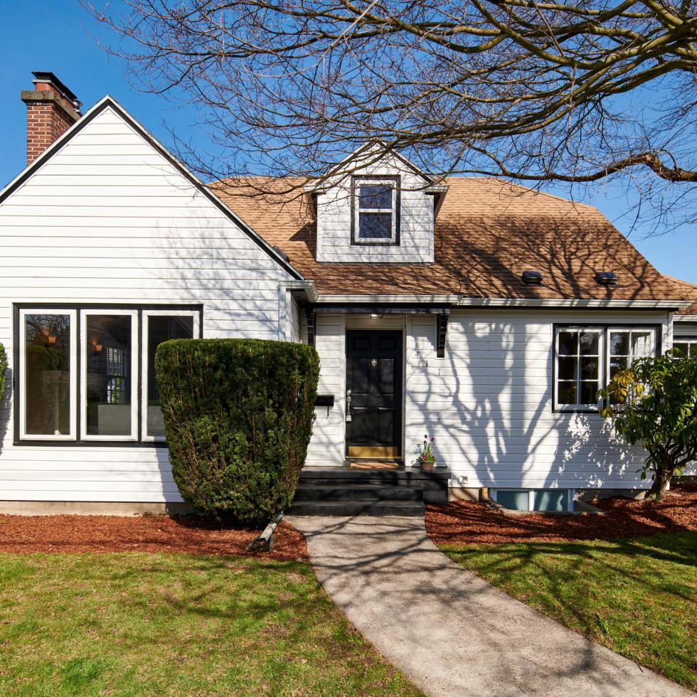 Exterior Bungalow of Piedmont house for sale in Portland Oregon green grass white house tree