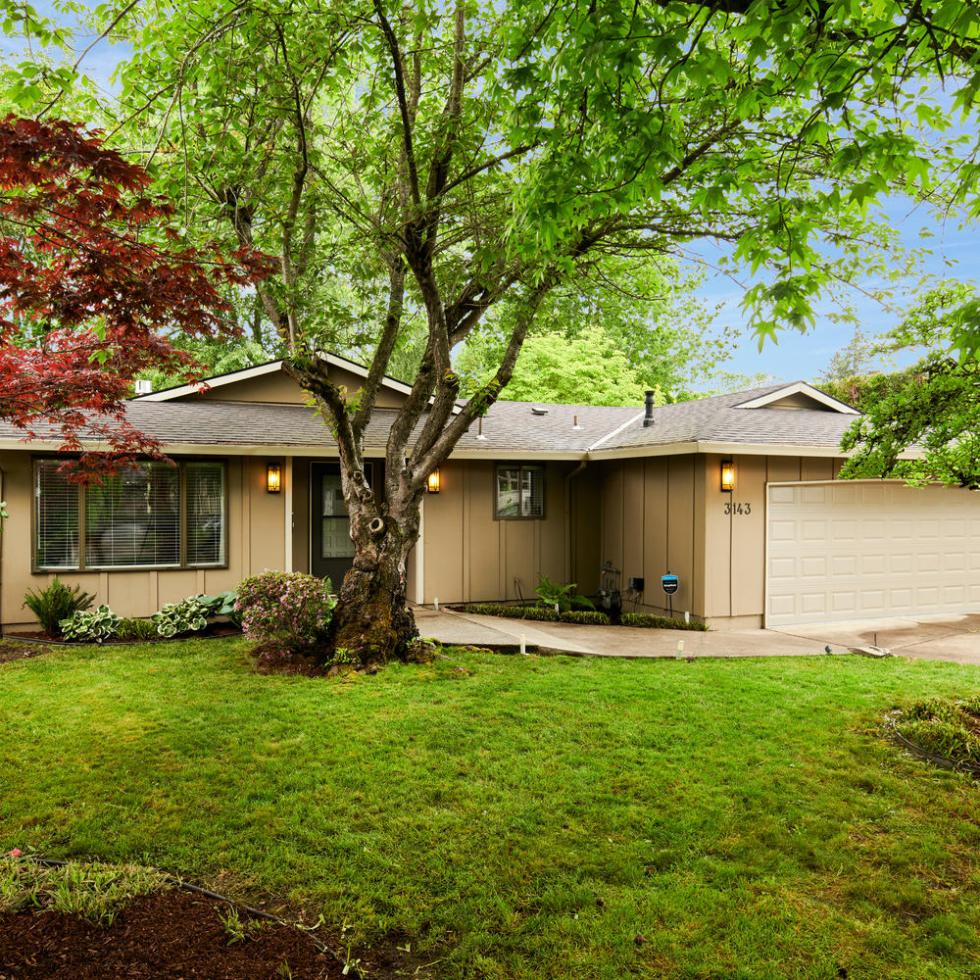 Exterior of house for sale in Portland Oregon in Laurelhurst with tree, grass and garage