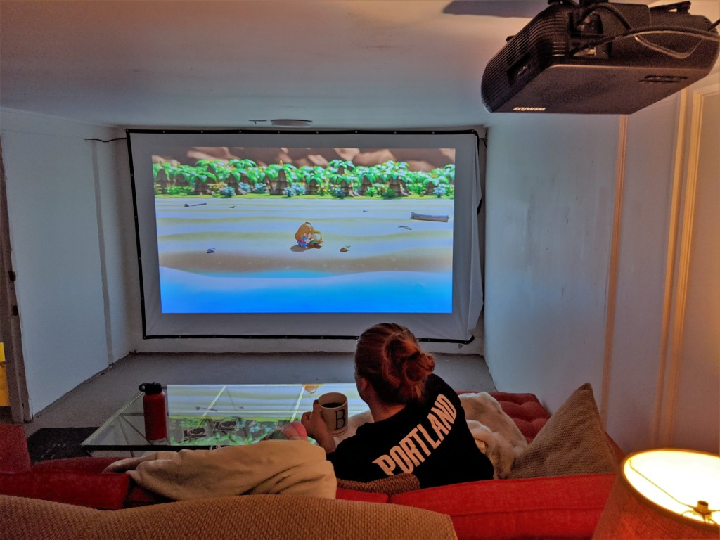 Basement with large screen on far war with a video game image projected on it. Woman sitting on couch playing the game.